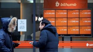 Men talk in front of an electric board showing exchange rates of various cryptocurrencies at Bithumb cryptocurrencies exchange in Seoul, South Korea, January 11, 2018.