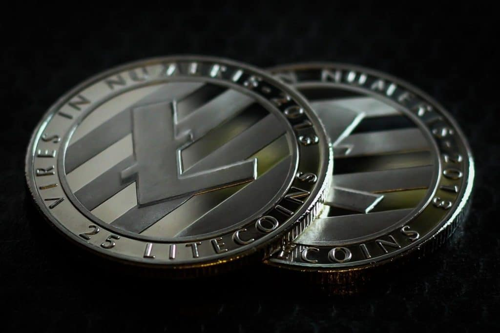 Two silver coins with litecoin L logo on the faces